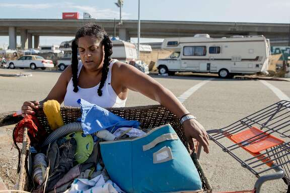 Nikki Cooper works to haul trash to the corner near the 5th Street Natives homeless encampment along 5th Street near West Oakland Bart in Oakland, Calif. Friday, Oct. 18, 2019.