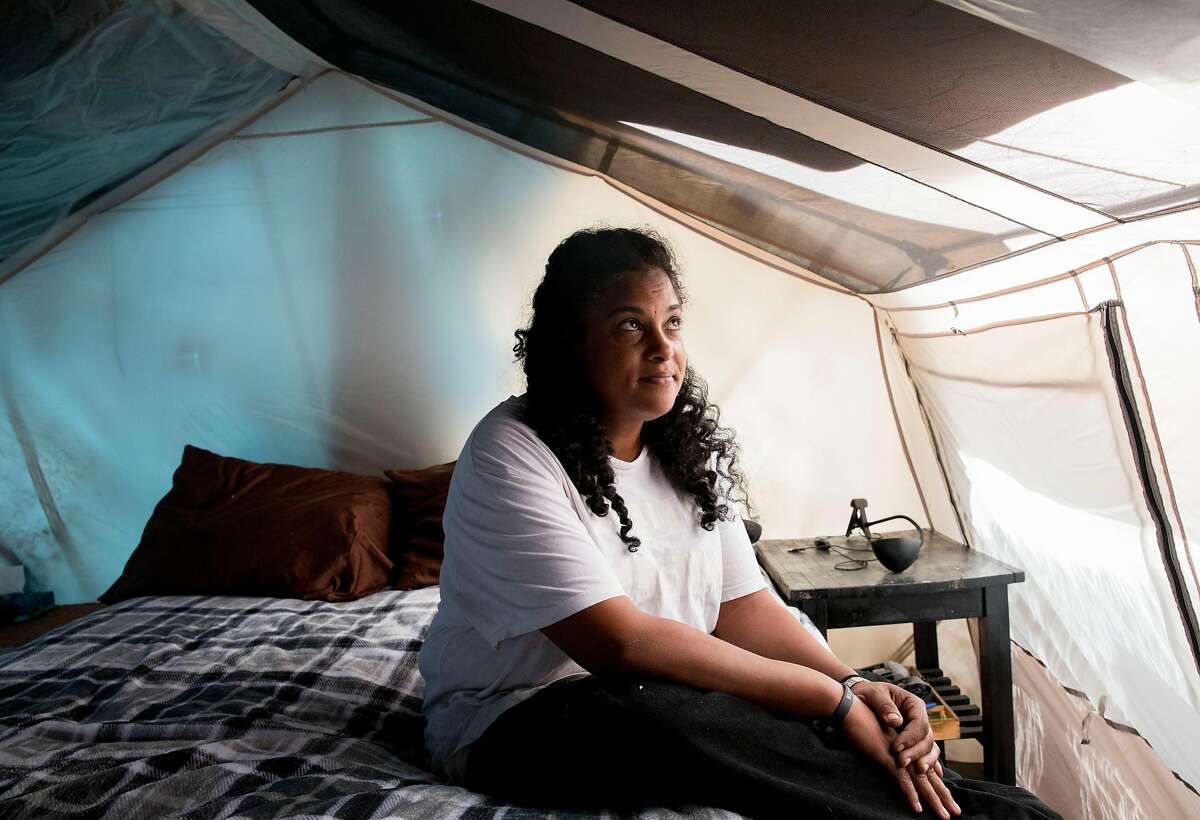 Nikki Cooper poses for a portrait inside her bedroom at the 5th Street Natives homeless encampment along 5th Street near West Oakland Bart in Oakland, Calif. Wednesday, Oct. 16, 2019.