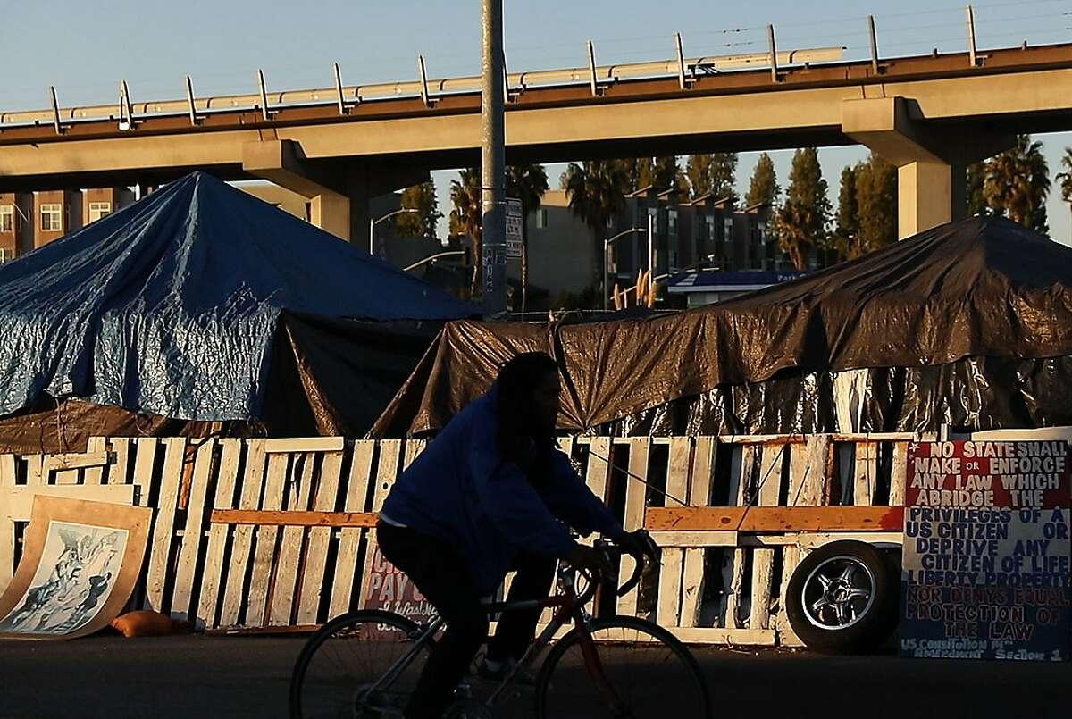 A man bikes past the 5th Street Natives homeless encampment seen at sunset along 5th Street near West Oakland Bart in Oakland, Calif. Thursday, Oct. 24, 2019.