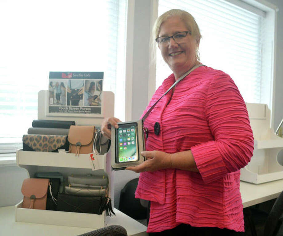 Edwardsville resident Tami Lange, founder and designer of Save the Girls, holds one of the touch screen phones that her company sells at its office and warehouse in Belleville. Photo: Scott Marion | The Intelligencer