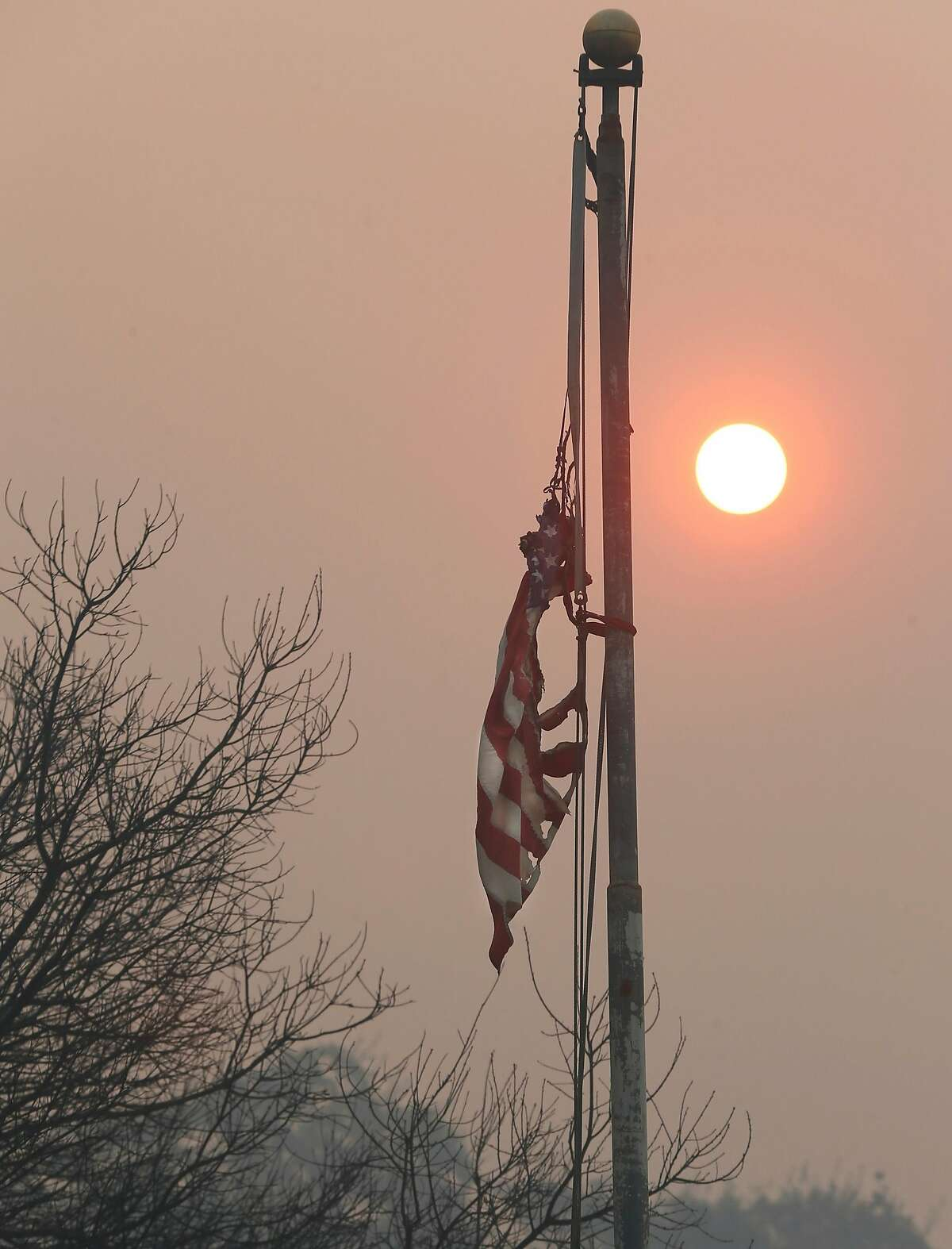 A singed American flag still hangs from a pole at a home on Geysers Road as the Kincade Fire continues to burn near Geyserville, Calif. on Friday, Oct. 25, 2019.