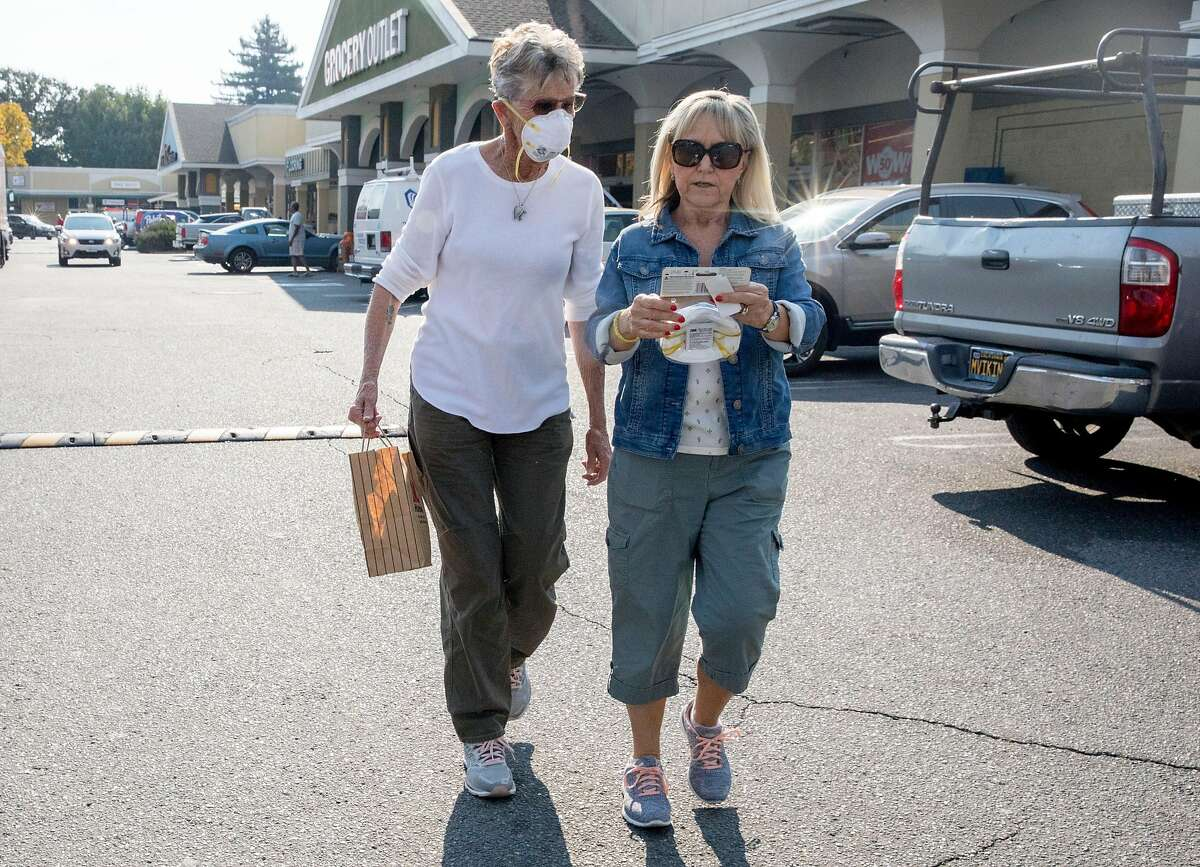 Dinah Mattos, 76, of Novato (left) sports a respirator mask while walking with Susan Blow of Penngrove after purchasing more masks at Pini Ace Hardware in Novato, Calif. Friday, Oct. 25, 2019 in response to poor air quality due to smoke from the Kincade Fire in northern Sonoma County.