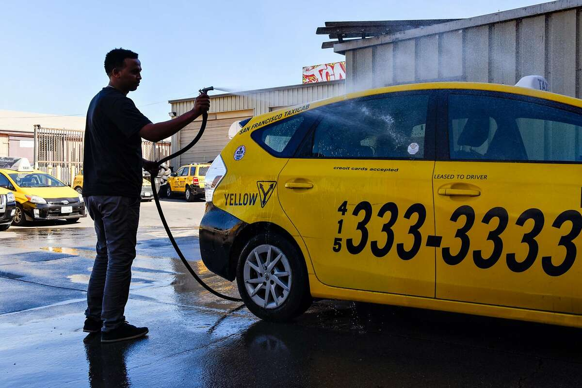 Ayenom Gebremedhin washing a taxi cab in the mechanic shop at Yellow Cab headquarters in San Francisco on October 23, 2019 in San Francisco, Calif.