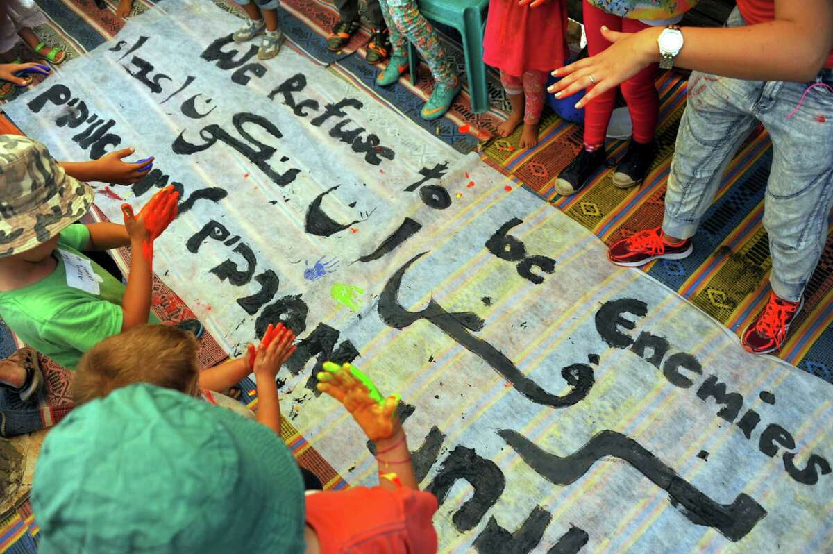 Roots includes a youth group with Palestinian and Jewish West Bank residents can get to know each other and talk. They made a banner proclaiming their determination to conquer animosity.