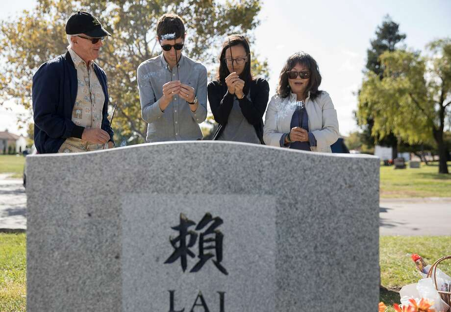 Steve Bitker (left), Jeremy B. White, Janelle Bitker and Alice Lai-Bitker offer incense at Cedar Lawn Cemetery in Fremont. Photo: Jessica Christian / The Chronicle