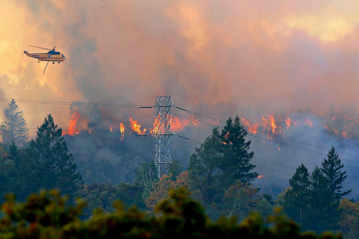 Helicopters dump water down to the Kincade Fire off of Pine Flat Road on Friday, Oct. 25, 2019, east outside of Geyserville, Calif.