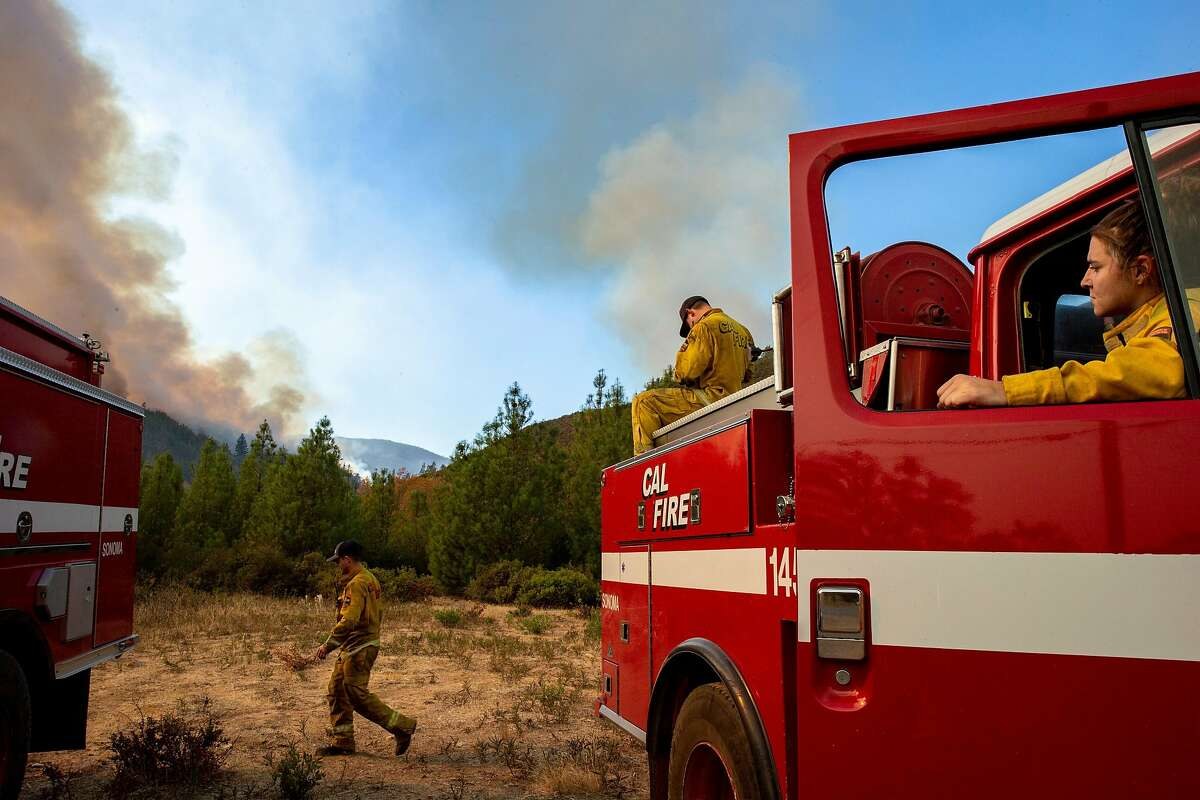 From left: Cal Fire Healdsburg's Daniel Frazee, Andrew Rush and Kassidy Harms watch as helicopters pass by and dump water down to the Kincade Fire off of Pine Flat Road on Friday, Oct. 25, 2019, east outside of Geyserville, Calif.