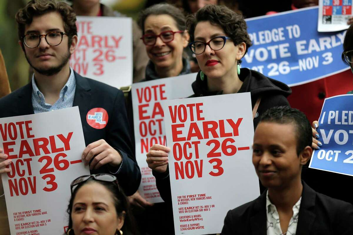 People hold signs during a rally to promote early voting in New York, Tuesday, Oct. 22, 2019. Early voting is set to happen for the first time in New York, and advocates hope the benefits of expanded ballot box access will outweigh the cost and headaches of keeping the polls open for more than a single day. Starting Saturday, voters in this autumn's election can cast ballots at select polling locations through Nov. 3. (AP Photo/Seth Wenig)