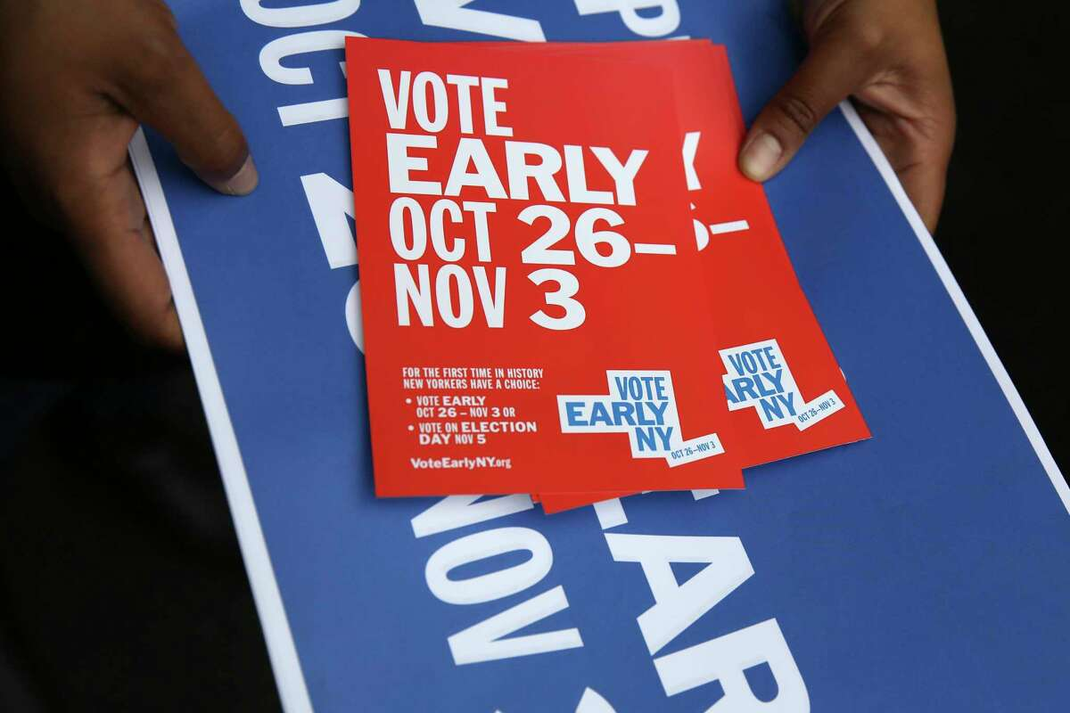 A woman hands out postcards and posters with information about early voting at a rally in New York, Tuesday, Oct. 22, 2019. Early voting is set to happen for the first time in New York, and advocates hope the benefits of expanded ballot box access will outweigh the cost and headaches of keeping the polls open for more than a single day. Starting Saturday, voters in this autumn's election can cast ballots at select polling locations through Nov. 3. (AP Photo/Seth Wenig)