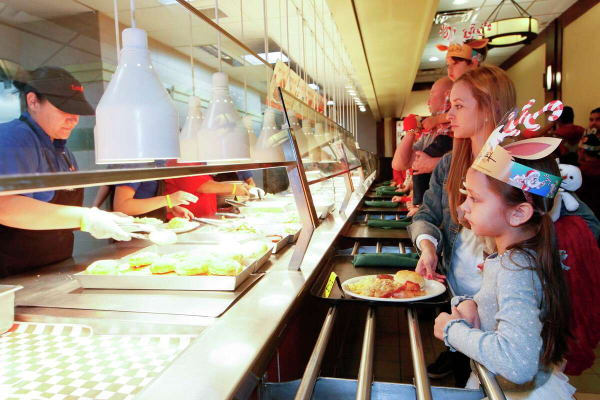 The Burkett family, Saleen (7, from right), April, James (4) and Anthony, wait in line for breakfast during