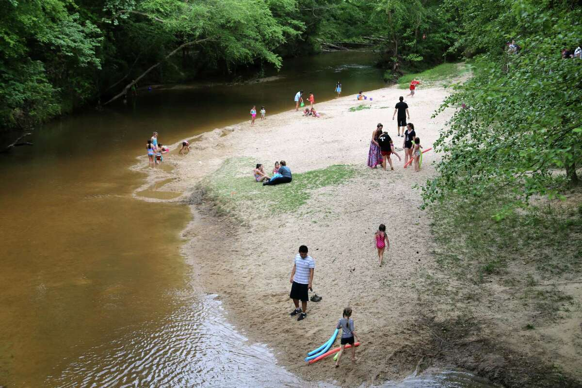 Peach Creek Overlook is often a popular location in the park for swimming and fishing. Hollenbeck recommends if visitors plan to stop at this area in the park, to spread out and come with immediate family. Photo: Parents, kids and pets enjoy an afternoon on Peach Creek in Lake Houston Wilderness Park, which the city acquired from the state parks system 10 years ago. (Mike Snyder/Houston Chronicle)