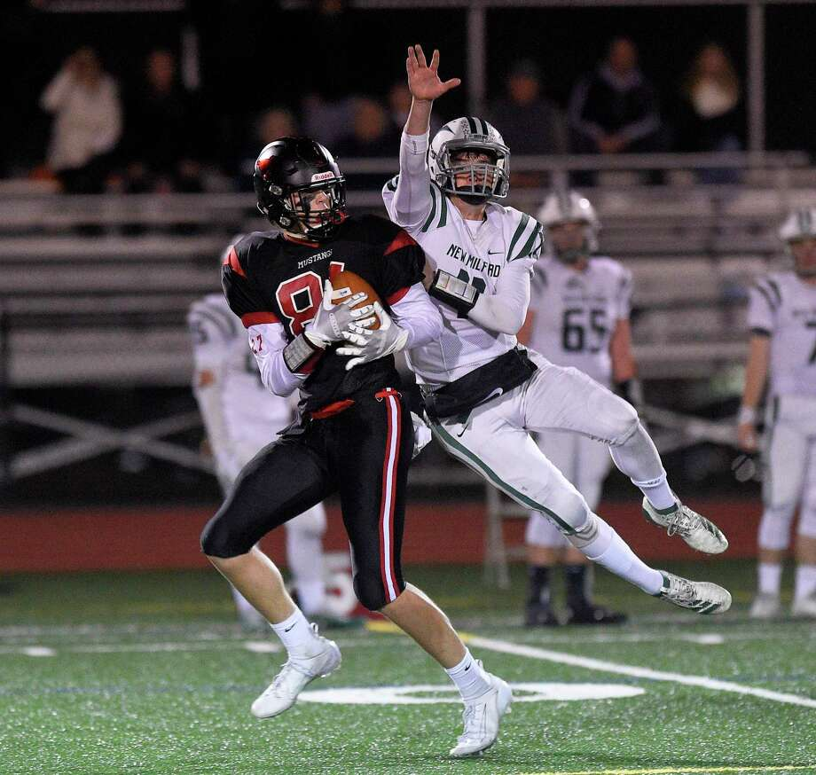 Fairfield Warde's Jack McKenna (81) makes a first-quarter reception against New Milford's Nathan Lawson (11) and carries the ball in for a 68-yard TD at Fairfield Warde High School in Fairfield on Friday. Warde won 34-21. Photo: Matthew Brown / Hearst Connecticut Media / Stamford Advocate