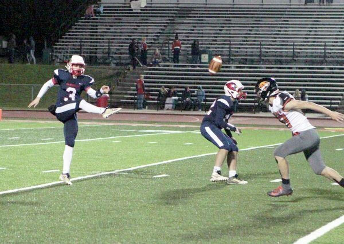 Big Rapids quarterback/kicker Sam Alley gets a punt away just in time during the Cardinals' regular-season finale with Alma on Friday night at Top Taggart Field. (Pioneer photo/Joe Judd)