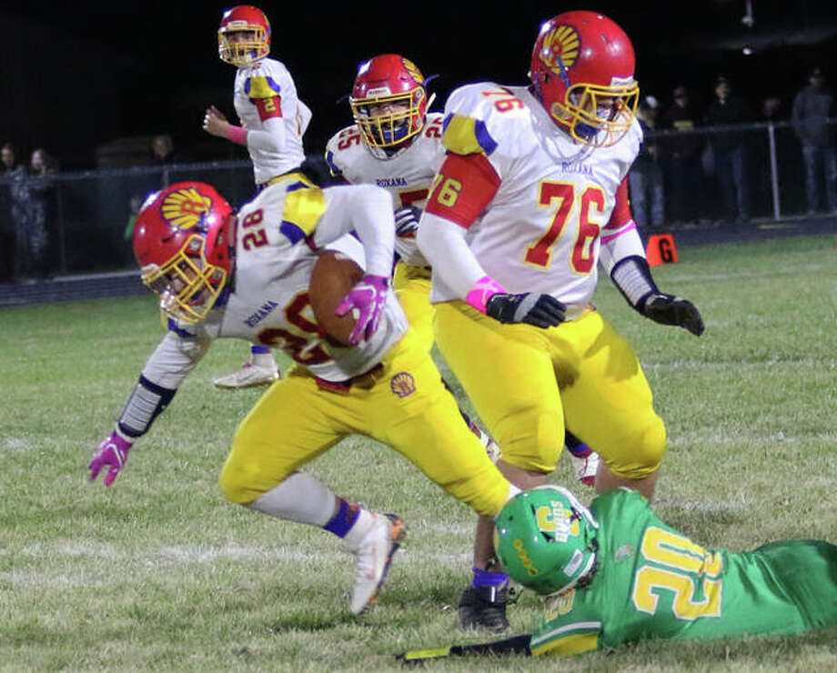 Roxana running back Michael Ilch (28) runs through the tackle attempt by Southwestern's Pauly Garrett after cutting off the block by Adam Coles (76) on Friday night at Knapp Field in Piasa. Photo: Greg Shashack / The Telegraph