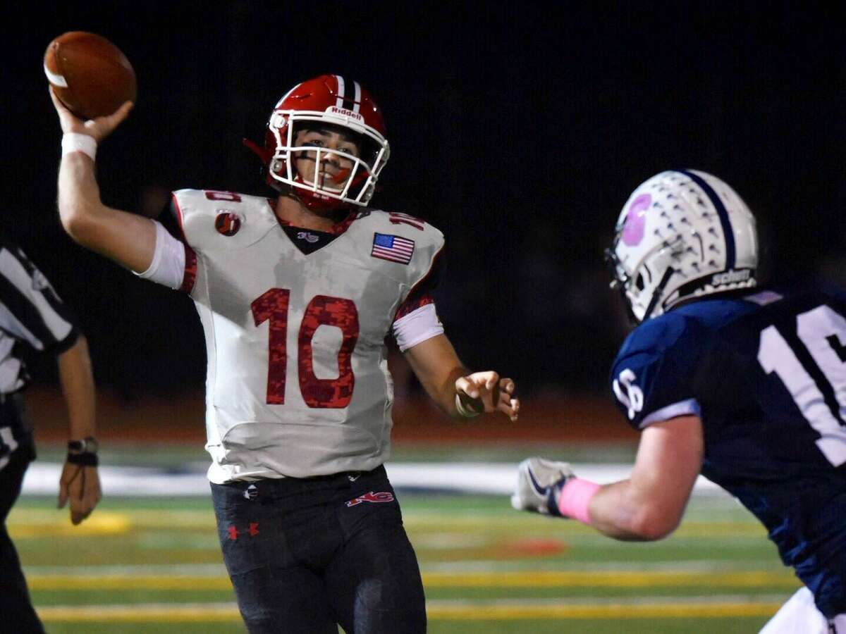 New Canaan's Drew Pyne (10) throws a pass while under pressure from Staples' Owen Clarke (16) during a football game at Staples High School on Friday, Oct. 25, 2019 in Westport, Conn.