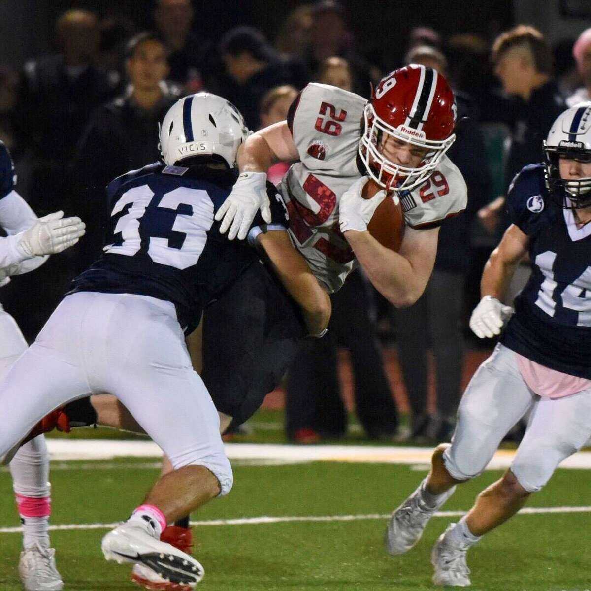 New Canaan's John Wise (29) is tackled by Staples' Nicholas Prior (33) during a football game at Staples High School on Friday, Oct. 25, 2019.