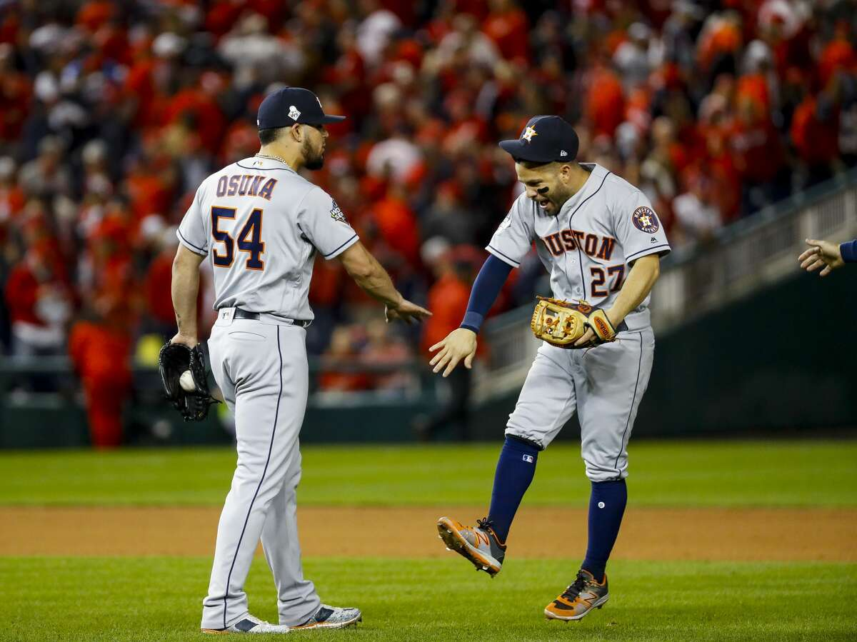 Houston Astros relief pitcher Roberto Osuna (54) and Houston Astros second baseman Jose Altuve (27) celebrate at the end of the ninth inning of Game 3 of the World Series at Nationals Park in Washington, D.C. on Friday, Oct. 25, 2019.
