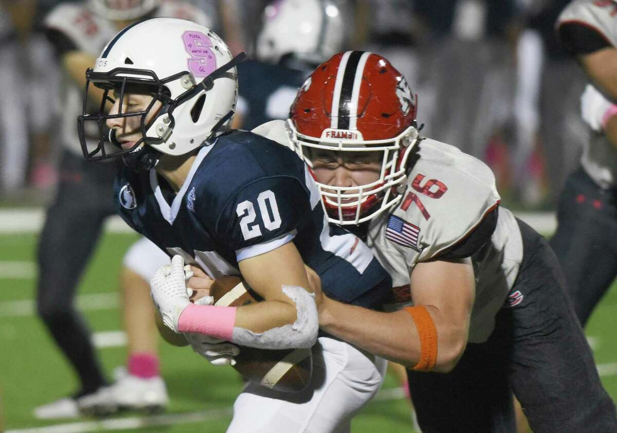 New Canaan's Matt Rigione (76) tackles Staples' Henry Beck (20) during a football game in Westport on Friday, Oct. 25, 2019.