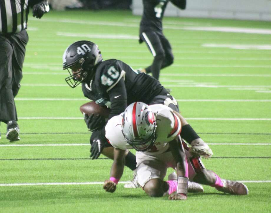 Memorial's Jayden Balderez (40) recovers a South Houston fumble deep in Trojans territory Friday night. It was one of two in the early minutes that helped create a 21-0 Mavs lead. Photo: Robert Avery