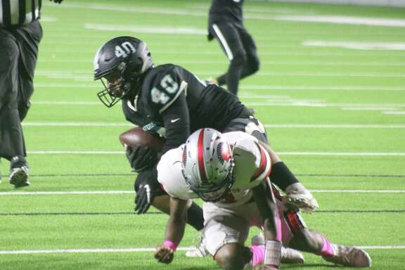 Memorial's Jayden Balderez (40) recovers a South Houston fumble deep in Trojans territory Friday night. It was one of two in the early minutes that helped create a 21-0 Mavs lead.