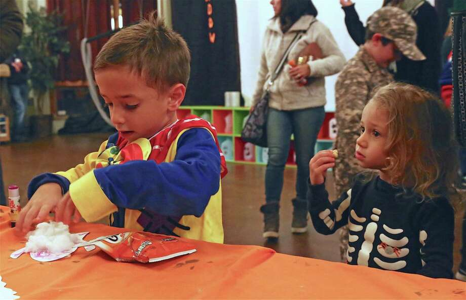 Sofia Calcagni, 3, of Fairfield, watches her brother Lucas, 5, work on a ghost craft project at The Connecticut Audubon Society's Enchanted Forest Halloween event on Friday, Oct. 25, 2019, in Fairfield, Conn. Photo: Jarret Liotta / Jarret Liotta / ©Jarret Liotta