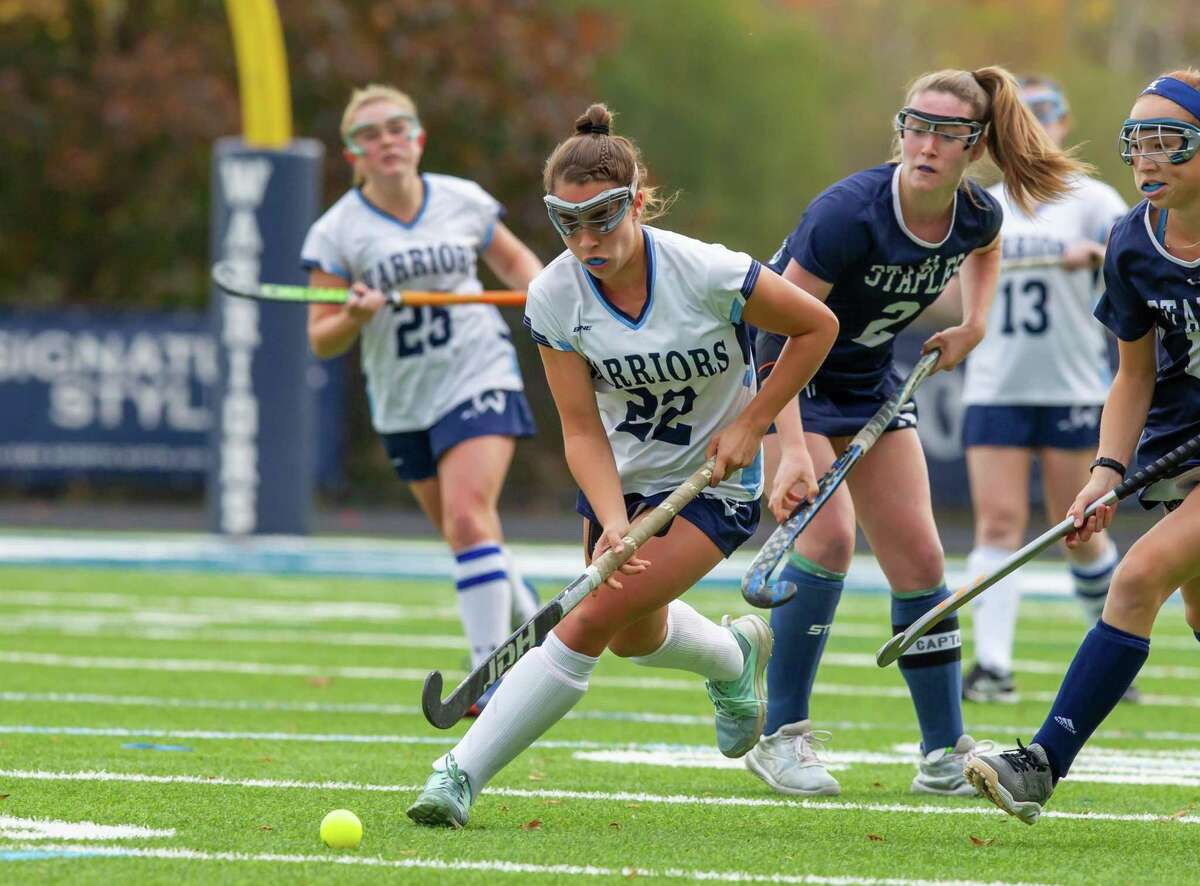 Wilton's Olivia Hahn cuts between Staples' Kyle Kirby (#2) and Laine Ambrose during Friday's field hockey game.