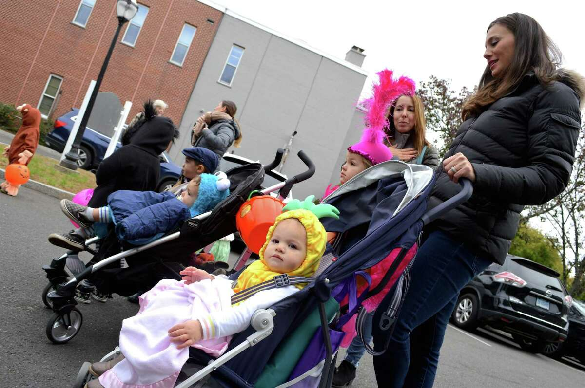 Arden Kearney, 1, of Darien, waits near the firehouse for the trick or treating to start at the Darien Community Association's annual Halloween parade, Friday, Oct. 26, 2018, in Darien, Conn.