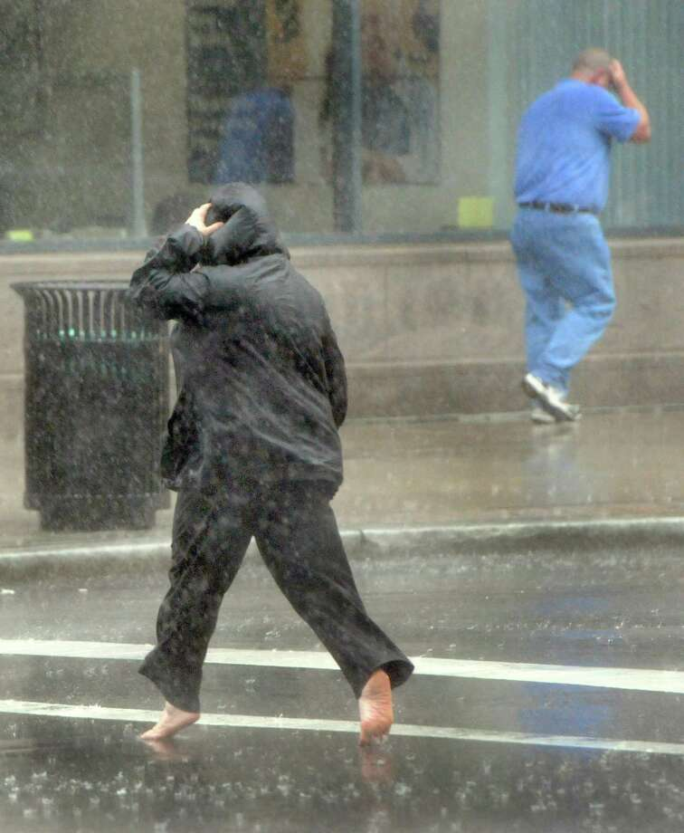 A woman runs barefoot through the crosswalk Wednesday afternoon May 8, 2013 on the corner of Church and Grove Street in New Haven during a torrential rain. Photo by Peter Hvizdak / New Haven Register Photo: Peter Hvizdak / New Haven Register / ©Peter Hvizdak /  New Haven Register