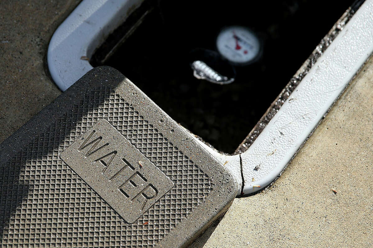 FILE - A cover sits next to a water meter on April 7, 2015 in Walnut Creek, California. EBMUD is preparing its customers for issues during the electricity shut-offs from PG&E, and is asking that people minimize water use.
