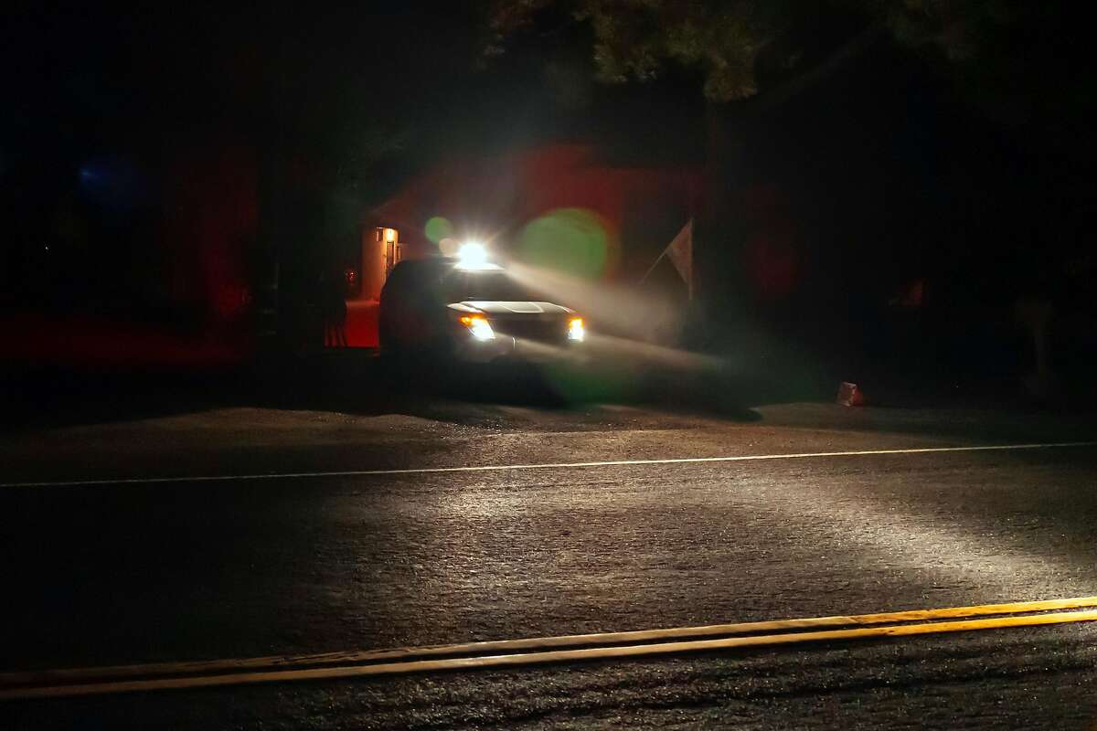 A police officer leaves a home after placing an evacuation order in the mailbox on Saturday, Oct. 26, 2019, in Geyserville, Calif.