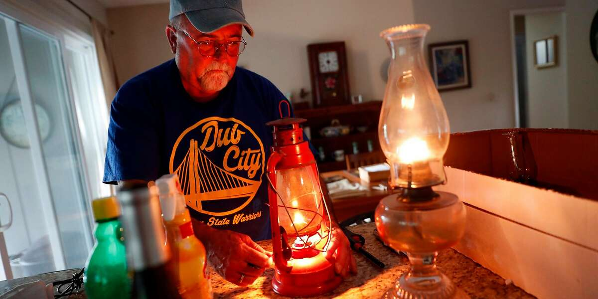 As the sun sets, Ken Garcia lights lanterns during PG&E power shut-off at his Oakmont home in Santa Rosa, Calif., on Wednesday, October 23, 2019.
