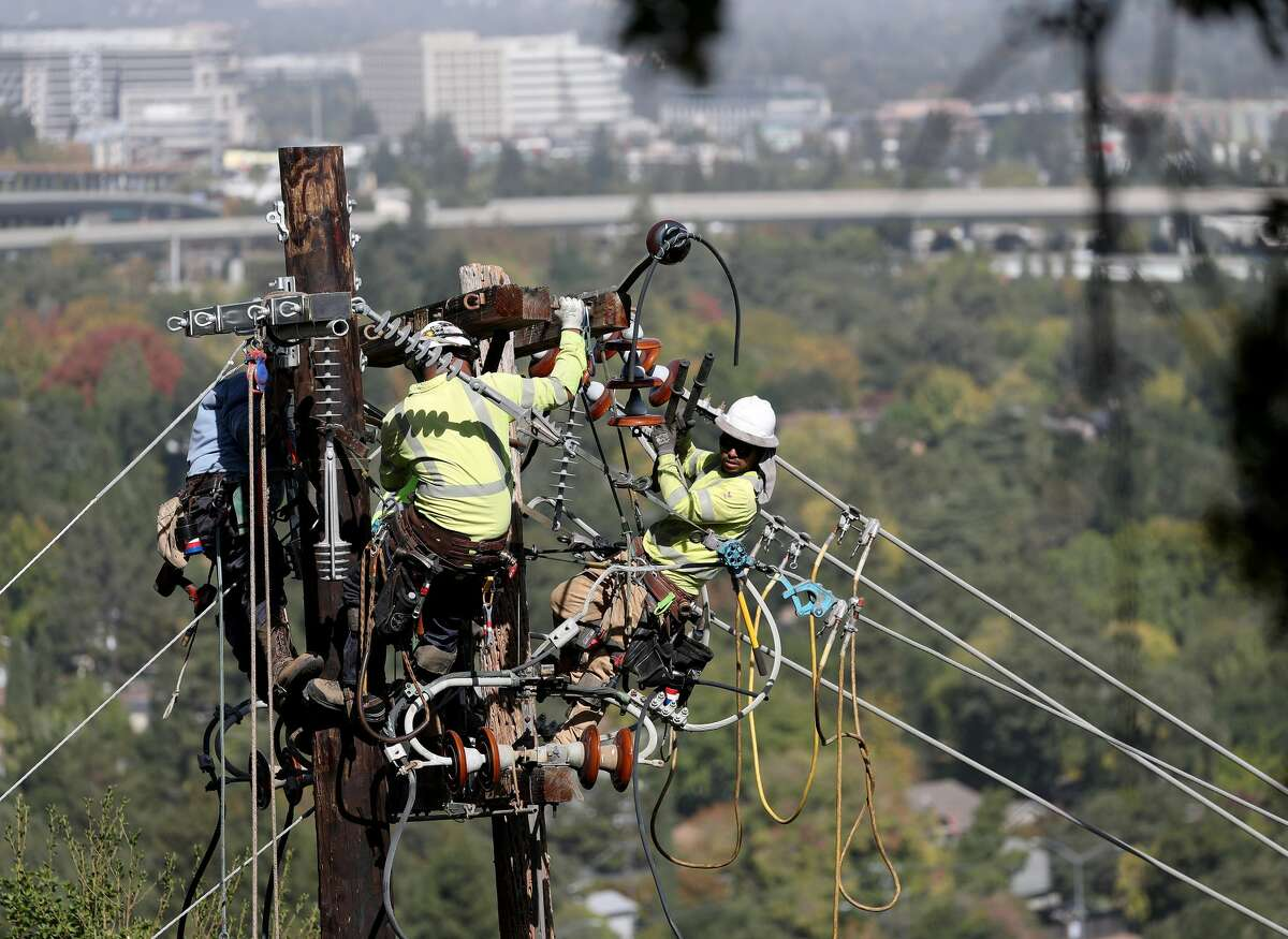 PG&E workers replace a power pole on a hillside at the Rossmoor senior community in Walnut Creek on Wednesday, Oct. 23, 2019. PG&E replaced the pole, which had been the source of several small fires, after outcry by Tim O'Keefe, chief executive officer of the Golden Rain Foundation and manager of Rossmoor.