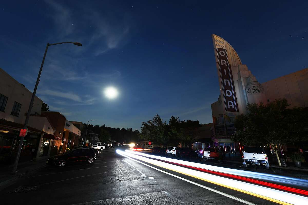 Without electricity the marquee of the Orinda Theatre remains dark as vehicles make their way down Moraga Way in Orinda, Calif., on Thursday, Oct. 10, 2019. Business continue to be closed due to the recent PG&E shutdown. PG&E began restoring power to Bay Area residents Thursday, taking the first steps in what could be a days-long process to end an outage that left many homes and businesses in the dark. (Jose Carlos Fajardo/East Bay Times via AP)