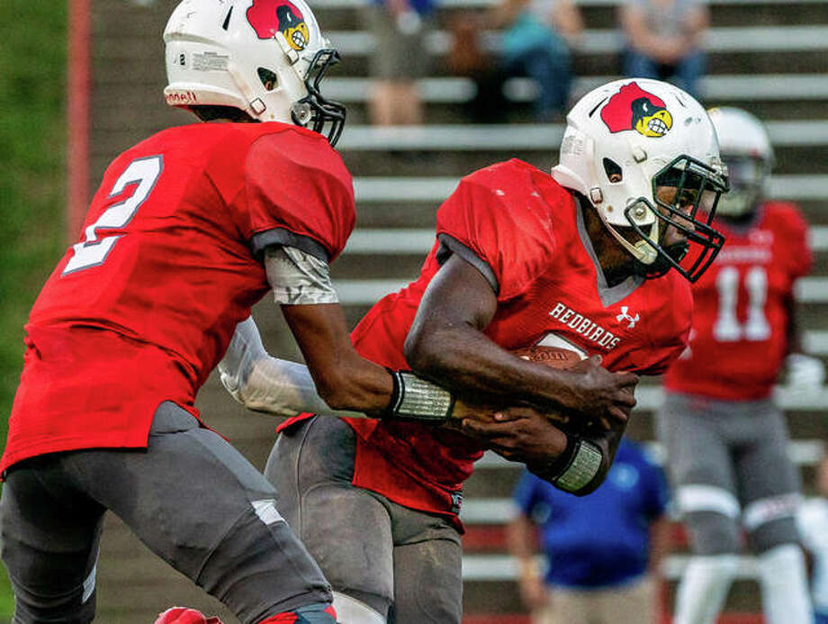 Alton's Tim Johnson scored on a 74-yard run Friday in the Redbirds' loss to DeKalb in the regular-season finale. He is shown taking a handoff from Andrew Jones earlier this season. Photo: Telegraph File