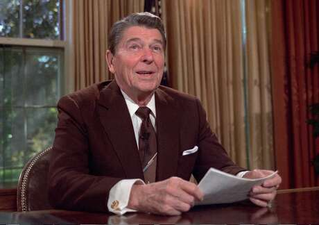 President Ronald Reagan works at his desk in the oval office of the White House as he prepares a speech on tax revision in an undated photo.
