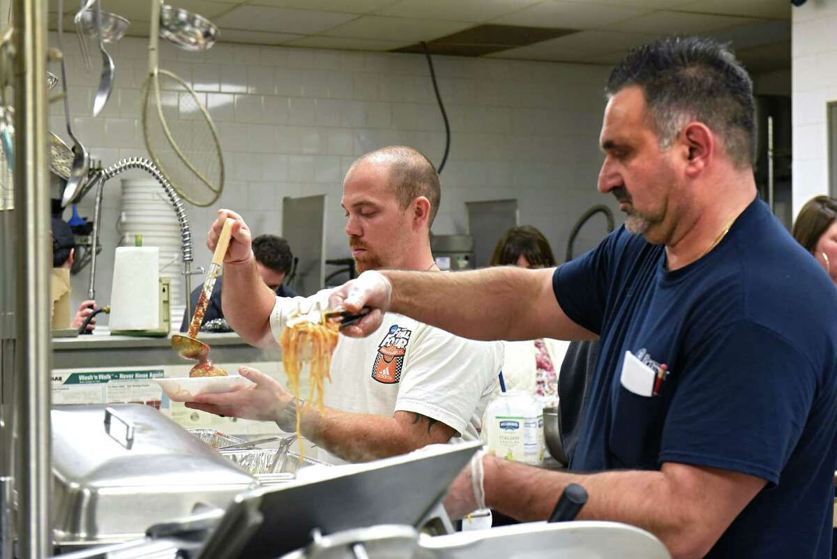 AJ Pasinella, left, and Michael Yamin plate food in the kitchen during a traditional pre-election day spaghetti & meatball supper at the Italian Community Center on Monday, Nov. 5, 2018 in Troy, N.Y. The dinner, originally held at the now closed St. Mary's Church, benefits the ICC Soup Kitchen, St. JosephA?•s and the Roarke Center food pantries, Christ Sun of Justice food collection and the Father Harry Scholarship Fund at LaSalle Institute. (Lori Van Buren/Times Union)