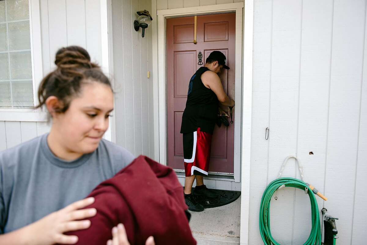 Luis Carrillo locks the front door as he and his wife Adriana Carrillo evacuate their home in Windsor, California, on Saturday, Oct. 26, 2019.