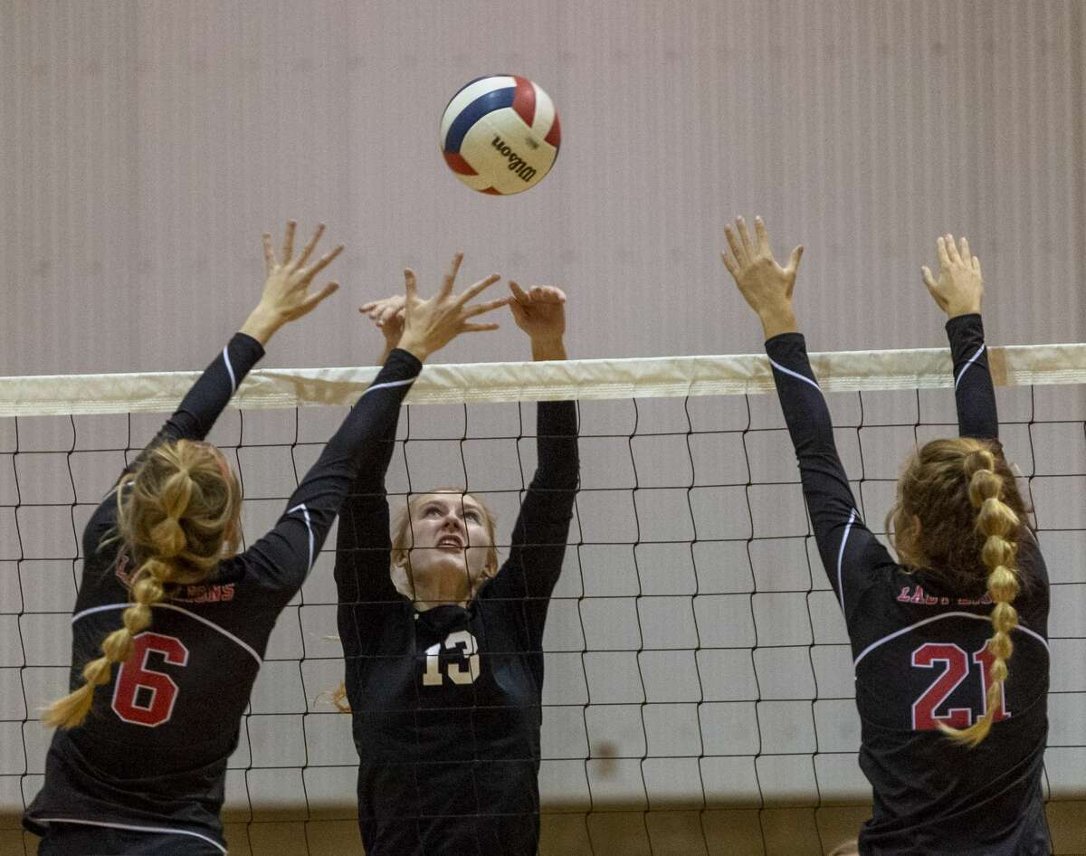 Midland Classical's Marin Casey (13) tips the ball between Central Texas Christian's Elizabeth Wood (6) and Amy Lucas (21) on Saturday, Oct. 26, 2019 at Midland Classical Academy.