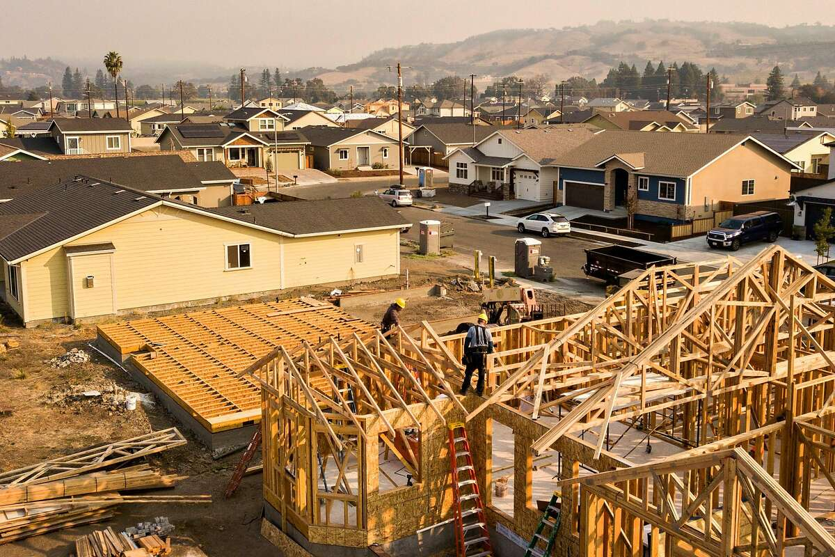 Prestige Home and Remodel Inc. workers build a home in the Coffey Park neighborhood as the Kincade Fire smoke fills the air on Friday, Oct. 25, 2019, Santa Rosa, Calif. The Coffey Park neighborhood continues to rebuild after it was destroyed in the Tubbs Fire of October 2017.