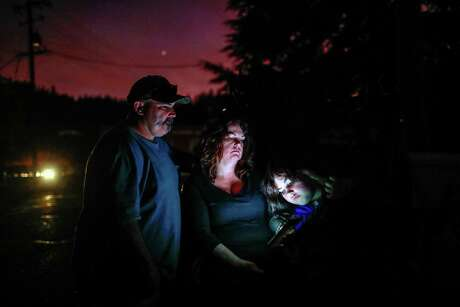 Aaron Johnson, wife Tammy White and daughter Leah Johnson, 11, sit outside their house without electricity Thursday as they watch the news on their phone for updates about the nearby Kincade Fire in Geyserville.