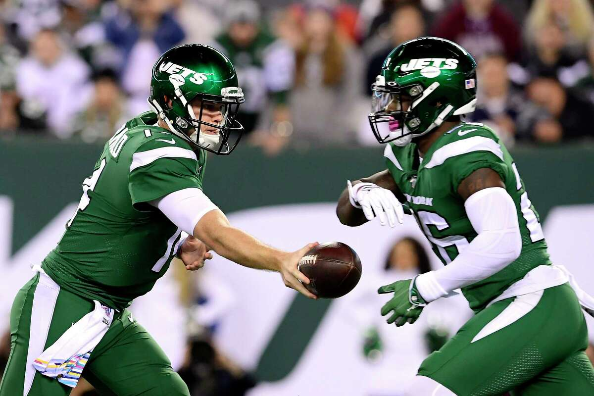 EAST RUTHERFORD, NEW JERSEY - OCTOBER 21: Sam Darnold #14 hands the ball off to Le'Veon Bell #26 of the New York Jets against the New England Patriots during the first half at MetLife Stadium on October 21, 2019 in East Rutherford, New Jersey. (Photo by Steven Ryan/Getty Images)