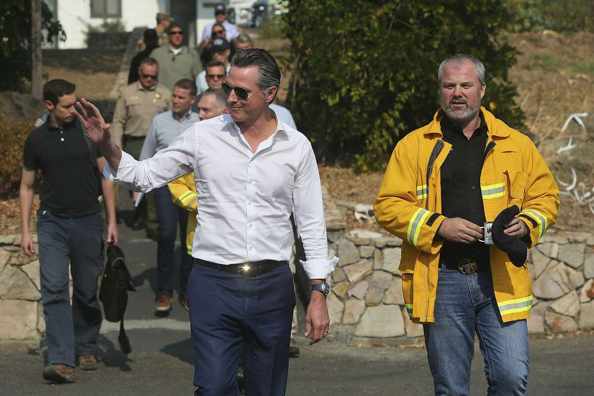 California Gov. Gavin Newsom, (center) and Sonoma County Supervisor James Gore arrive for a press conference at the Cal Fire Healdsburg Station on Friday, Oct. 25, 2019, near Geyserville, Calif. Newsom called on investor Warren Buffett buy the troubled utility, whose share price tanked again Monday.