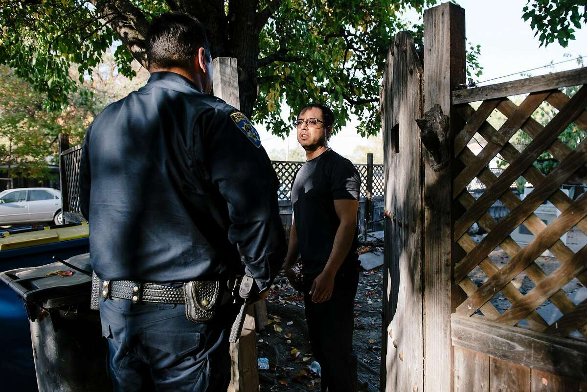 While checking if residents have heeded the mandatory evacuation notices, Officer Tony Wold with the California Highway Patrol's Valley Division, left, speaks with resident Ubdlao Molina who said he is waiting for his father to show up before evacuating, in Windsor, California, on Saturday, Oct. 26, 2019.