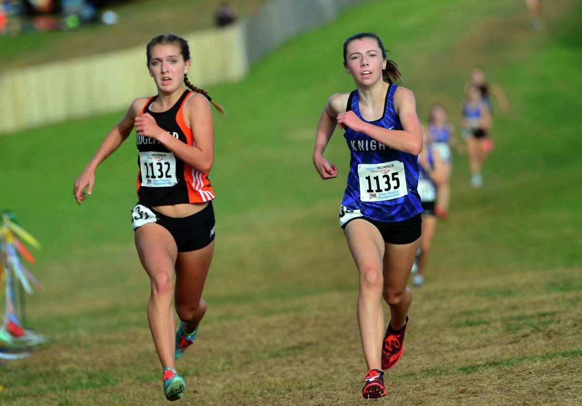 Ridgefield's Tess Pisanelli, left, and Southington's Jacqueline Izzo run neck and neck to the finish line during Class LL cross country championship action in Manchester, Conn., on Saturday Oct. 26, 2019.