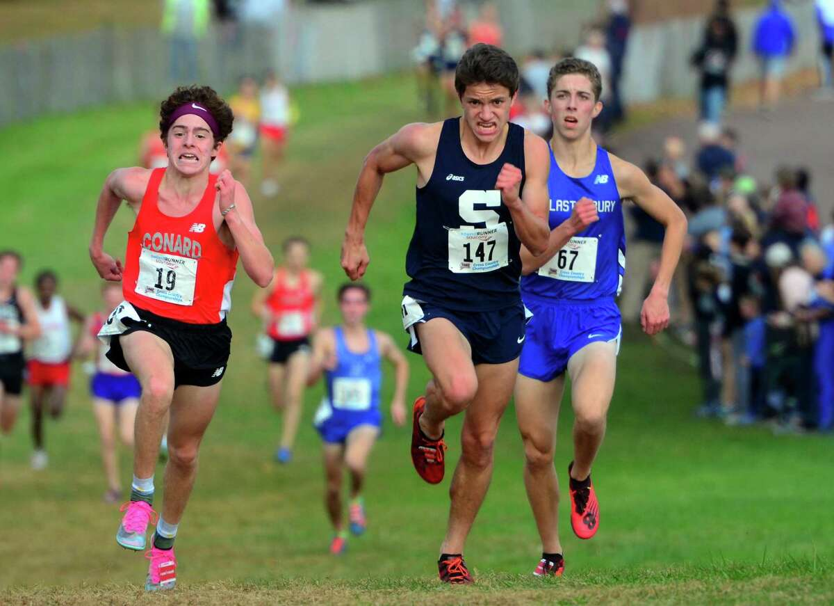 Staples' Morgan Fierro, center, stays ahead of Conrad's Callum Sherry, left, and Glastonbury's Jacob Slith to cross the finish line for third place during Class LL cross country championship action in Manchester, Conn., on Saturday Oct. 26, 2019.