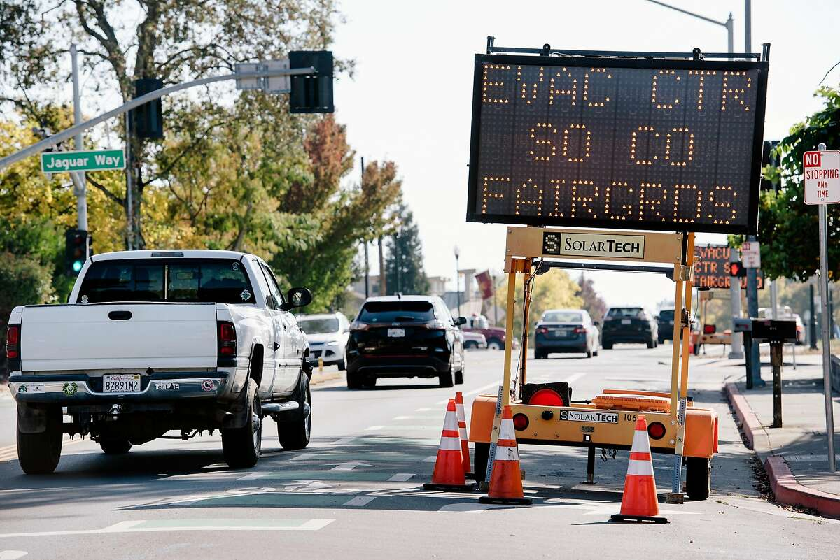 A line of vehicles passes a sign displaying information about evacuations in Windsor, California, on Saturday, Oct. 26, 2019.