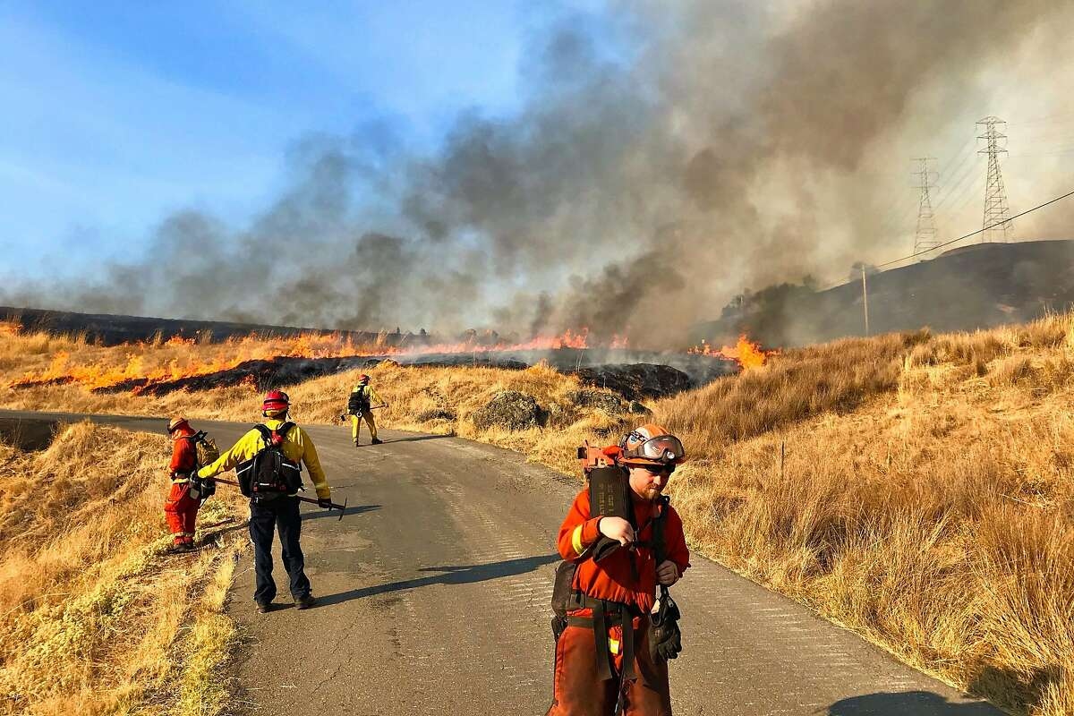 Firefighters light back-fires along Pine Flat Road near Geyserville, Calif. on Saturday, October 26, 2019 to head off the Kincade Fire, which has grown to more than 25,000 acres and triggered mandatory evacuations in Windsor, Geyserville and Healdsburg.