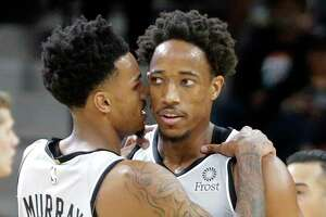 Dejounte Murray has a quick chat with DeMar DeRozan as the Spurs host the Wizards at the AT&T Center on 26, 2019.