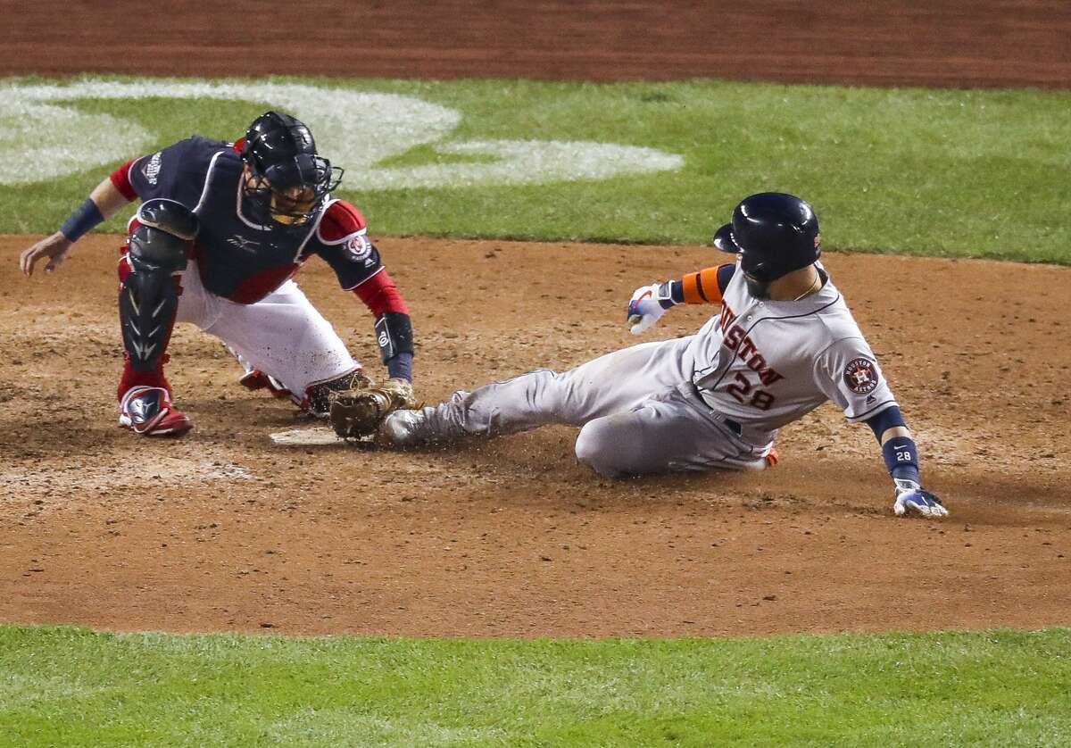 Washington Nationals catcher Yan Gomes (10) tags Houston Astros catcher Robinson Chirinos (28) out at home on a single by Houston Astros center fielder Jake Marisnick (6) during the ninth inning of Game 4 of the World Series at Nationals Park in Washington, D.C. on Saturday, Oct. 26, 2019.