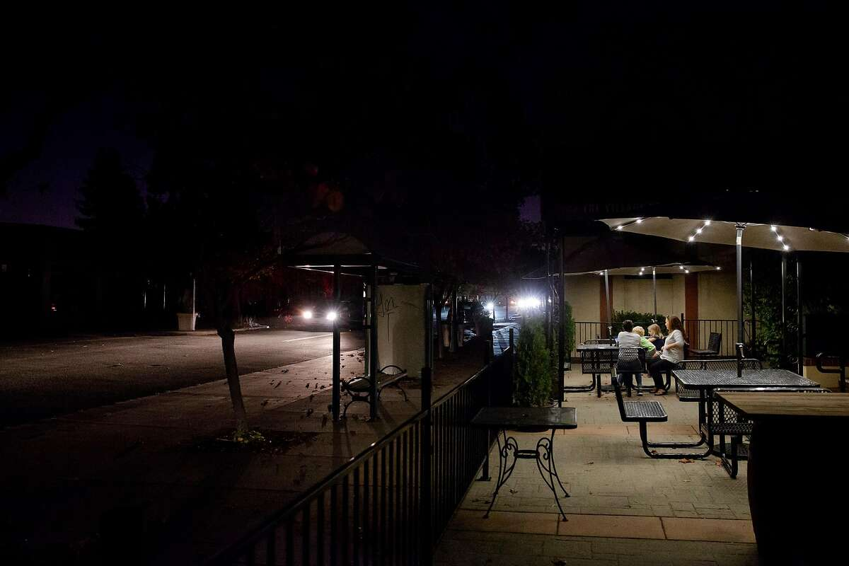 Tracie PIxton, owner of The Village Restaurant sits under solar powered umbrella lights with her children in Novato, Calif. during PG&E's Marin County power shut down on Saturday, Oct. 26, 2019. Pixton was able to keep her restaurant open Saturday night thanks to two back up generators that kept the kitchen lit along with a few strands lights hung from the ceiling. Residents throughout the North Bay are expected be without power starting Saturday evening as PG&E begins it's second Public Safety Power Shut-Off. PG&E states that over 940,000 residents will be without power through the weekend.